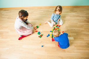 Three kids playing with wooden