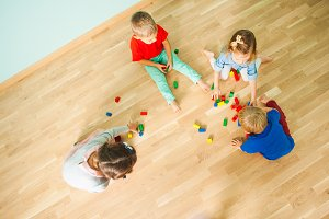 Four kids playing on the floor of