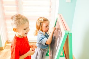 Happy kids writing on a blackboard