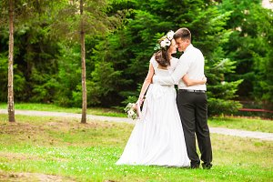 The bride gets married outdoors in