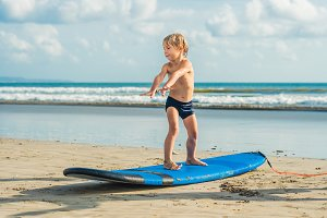 Little boy surfing on tropical beach
