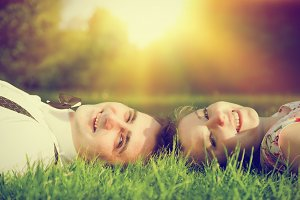 Smiling couple lying on summer grass