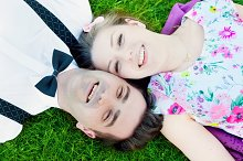 Happy couple lying on summer grass