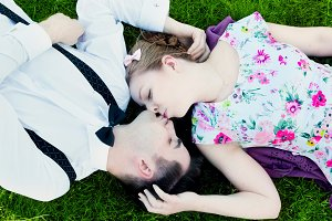 Couple kissing during lying on grass