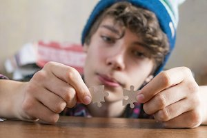 young person hands solving puzzle at