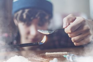 young drug addict heating heroin dps