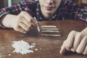 young narcotic drug addict rolling a