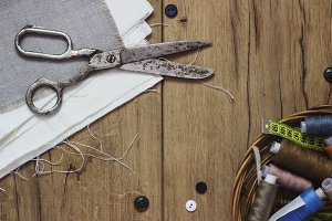 Sewing kit. Scissors, bobbins with thread and needles on the old wooden background