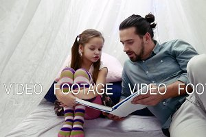 little girl and her father reading a