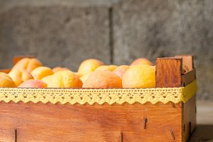 Wooden box full of ripe apricots.