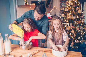 Family baking gingerbread cookies on