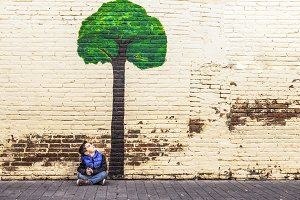 Little kid seated under a tree paint