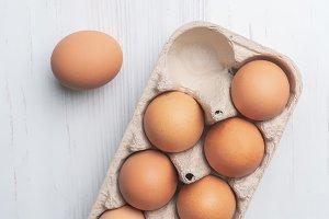 fresh eggs in paper tray on white su