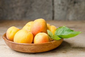 Wooden bowl full of ripe apricots.