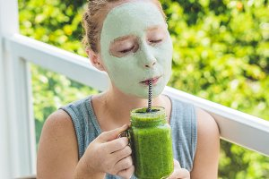 Spa Woman applying Facial green clay