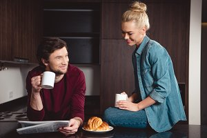 smiling couple holding coffee cups a