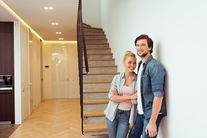 cheerful couple standing near stairs