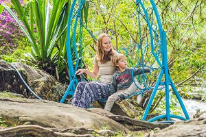 Mom and son on a swing in a tropical
