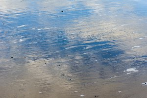 Reflection of clouds on wet sand
