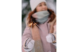 burning sparklers in woman's hands