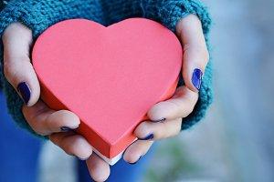 Female hands holding heart shaped gi