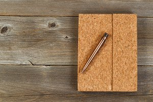 Retro pen and notepad on aged wood