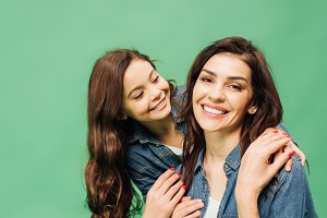 smiling mother and daughter in denim