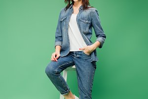 woman in denim sitting on chair and