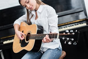 girl sitting and playing guitar in l