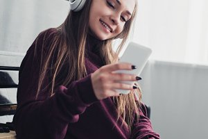smiling girl in headphones sitting a