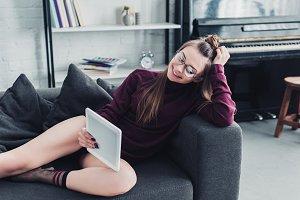smiling girl lying on sofa and using