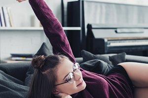 attractive girl lying on sofa, smili