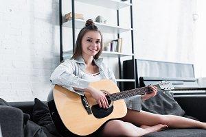 beautiful musician sitting on sofa,