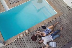 Couple relaxing near pool side