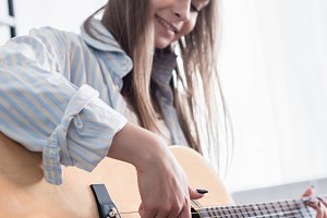 cheerful musician playing acoustic g