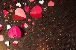 Flying red paper hearts on wooden