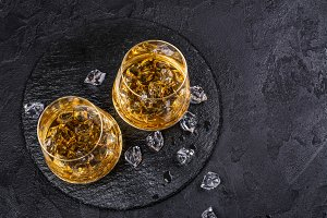 Two glasses of Cognac with ice cubes