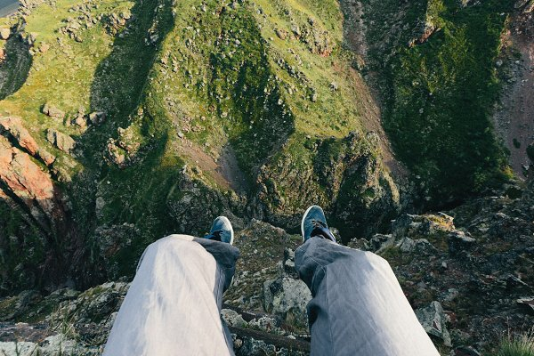 Sports Stock Photos - Traveler sits on the edge of a cliff