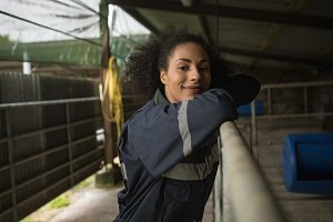 Happy female farmer standing in barn