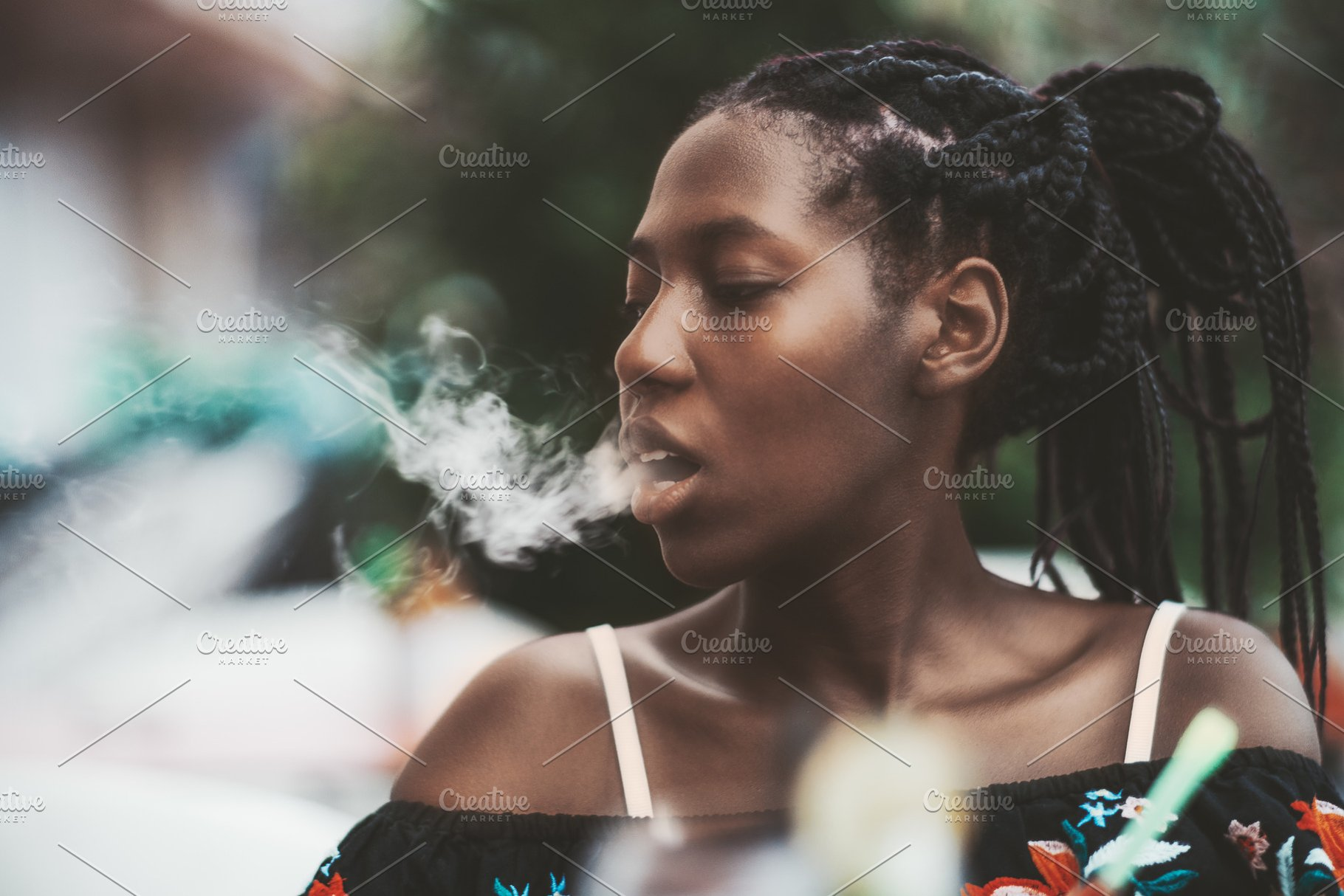 Black girl is exhaling hookah smoke