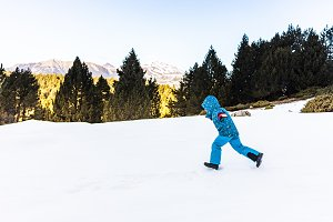 Boy running down a snowy mountain