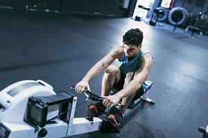 Man paddling on gym machine training