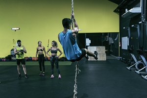 Man scales the rope in a gym while a