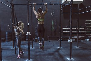Women training chins in gym in back