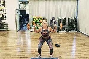 Woman training shoulder in gym lifti