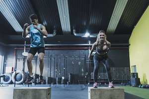 Couple training jumping on boxes at
