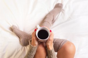 Woman sitting in bed drinking a cup