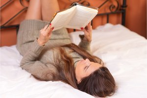 Woman lying in bed reading a book