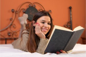 Woman in bed reading a book