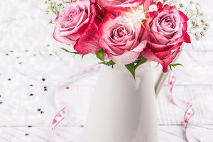 Pink roses in a white pitcher